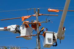 Working On Power Lines. Utility workers repair power lines from the safety of a bucket boom Royalty Free Stock Image
