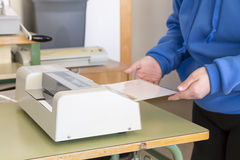 Working in print. Hands introducing a document laminating machine Stock Images