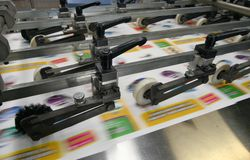 Working print machine. Colored brochures on working print machine royalty free stock photos