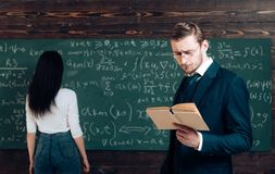 Working a problem in algebra. Doing sums. Teacher read book to girl student at chalkboard. Genius man and woman rear. Working a problem in algebra. Doing sums royalty free stock images
