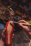Working process of a cobbler. Top view of a shoe sole gluing with a paintbrush royalty free stock image