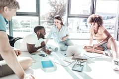 Relaxed young colleagues having pause. Working process. Handsome bearded men lying on the floor and leaning on elbows while talking to his friends royalty free stock photo