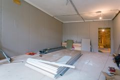 Working process of installing metal frames for plasterboard drywall for gypsum walls in apartment is under constructio. Working process of installing metal Royalty Free Stock Images