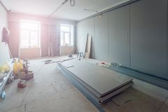 Working process of installing metal frames for plasterboard drywall for making gypsum walls in apartment is under construction. Working process of installing Stock Photography