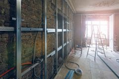 Working process of installing metal frames for plasterboard drywall for making gypsum walls with ladder and tools in apartment i. S under construction Stock Images