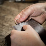 Working process of the leather bag. Or messenger in the leather workshop. Woman's hands holding the leather. Color tone image royalty free stock photos