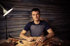 Working process of the leather belt in the leather workshop. Man holding crafting tool and working. Tanner in old. Tannery. Wooden table background. Close up Stock Photography