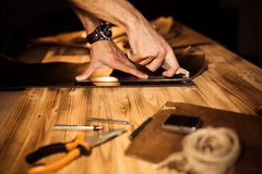 Working process of the leather belt in the leather workshop. Man holding crafting tool and working. Tanner in old. Tannery. Wooden table background. Close up Stock Images