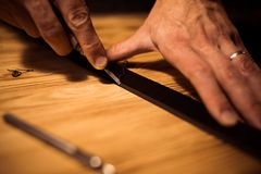 Working process of the leather belt in the leather workshop. Man holding crafting tool and working. Tanner in old. Tannery. Wooden table background. Close up Royalty Free Stock Photos
