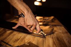 Working process of the leather belt in the leather workshop. Man holding crafting tool and working. Tanner in old. Tannery. Wooden table background. Close up Royalty Free Stock Image