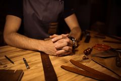 Working process of the leather belt in the leather workshop. Man holding hands on wooden table. Crafting tools on Stock Image