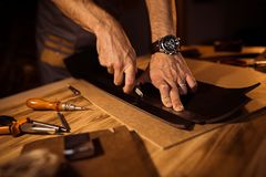 Working process of the leather belt in the leather workshop. Man holding crafting tool and working. Tanner in old. Tannery. Wooden table background Stock Photography