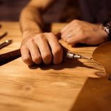 Working process of the leather belt in the leather workshop. Man holding crafting tool and working. Tanner in old. Tannery. Wooden table background. Close up Royalty Free Stock Photo