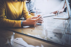 Working process in modern office.Woman looking to her mobile phone and sitting at the wooden table.Horizontal, blurred Royalty Free Stock Photo