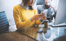 Working process in modern office.Woman looking to her mobile phone and sitting at the wooden table.Man typing on his Stock Photography