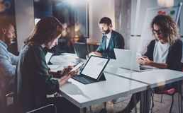 Working process photo.Group of young coworkers working together at night modern office loft.Teamwork concept.Blurred. Background.Horizontal Royalty Free Stock Images