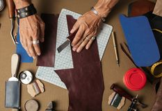 Working process of producing hand made leather wallet in the leather workshop. Moments of modelling design of custom made pocketbook. Workplace of Leather royalty free stock images