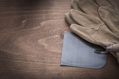 Working protective gloves and plastering trowel on vintage woode Stock Images
