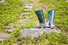 Working Rain Boots and Gloves on Rock Stock Photo