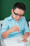 Working with reagent. Vietnamese boy working with reagent in the chemistry class Royalty Free Stock Image