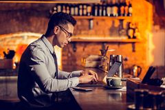 Businessman working remotely sitting at the bar stand. Working remotely. Businessman working remotely while sitting at the bar stand in his restaurant royalty free stock photography