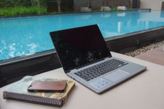 Working remotely by the pool on your laptop is the major benefit royalty free stock images