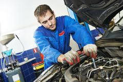 Working repairman auto mechanic. Auto repairman industry mechanic worker in car auto repair or maintenance shop service station Royalty Free Stock Photography
