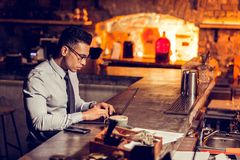 Busy businessman working remotely from his restaurant. Working in restaurant. Busy prosperous and rich businessman working remotely from his restaurant royalty free stock image