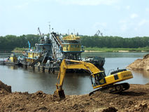 Working in the river. The excavator works in the sand-pit on the river bank. There are some working ships in the background royalty free stock photos