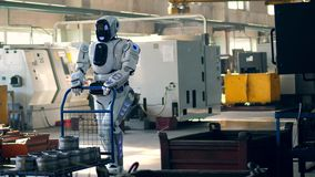 Working robot pulls a cart with metal boxes at a factory. 4K stock video