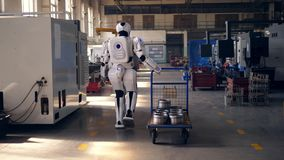 Working robot pulls a metal cart, walking in a facility. 4K stock video