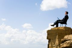Working on the rock. Image of pensive businessman sitting on the top of mountain with laptop and looking at the sky Royalty Free Stock Photo