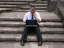 Working on rocks stairs. Man working with computer and speaking to the mobile phone on the rocks stairs Stock Image