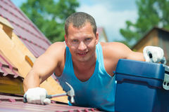 Working on the roof with a tool Royalty Free Stock Photo