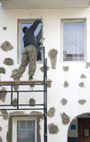 Working on scaffolding. A worker putting on new isolation on a wall, working at a window, standing on scaffolding royalty free stock images