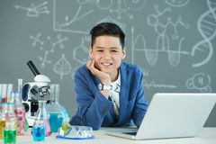 Working on School Research Project. Waist-up portrait of handsome boy with stylish haircut sitting at school desk and working on research project with help of Stock Photos