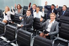 Working at seminar. Image of business people sitting in rows at seminar with raised arms Stock Images