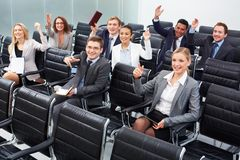 Working at seminar. Image of business people sitting in rows at seminar with raised arms Stock Photography