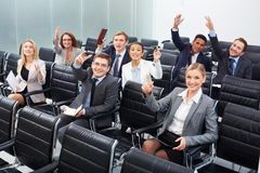 Working at seminar. Image of business people sitting in rows at seminar with raised arms Royalty Free Stock Photos