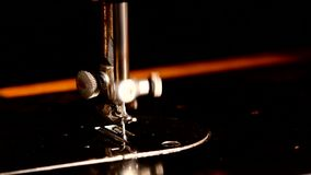 Working sewing machine isolated on black stock footage