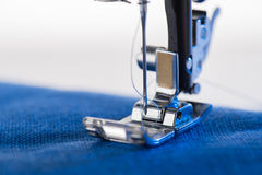 Working sewing machine sewing blue fabric. Close-up view of working sewing machine sewing blue fabric Stock Photo