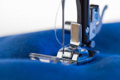 Working sewing machine sewing blue fabric. Close-up view of working sewing machine sewing blue fabric Stock Photos