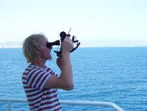 Working with sextant on board of merchant vessel for navigation. Working with sextant on board of a merchant vessel by duty officer to determinate the present Stock Image
