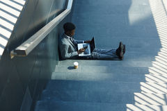 Working in shade. Busy salesman with laptop and smartphone sitting on stairs in shade royalty free stock photo