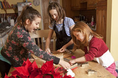 Working in a Small Space. Three sisters are working together in a small space to cut out gingerbread dough into shapes and place them on a baking tray. They royalty free stock photography