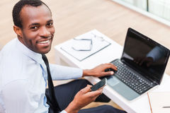 Working with smile. Top view of young African man in formalwear working on laptop and smiling while sitting at his working place Stock Image