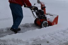Snow blowing a driveway on a blustery winter day Stock Images