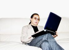 Working on a sofa 01. The man working on laptop royalty free stock images