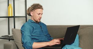 Working on Sofa. Stylish man with dreads hair working on laptop sitting on the grey sofa stock video