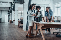 Working through some concepts. Group of young business people working together in creative office while standing near the wooden desk Stock Photos
